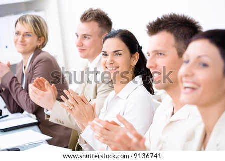 Five business people sitting in a row, smiling and clapping on business training. Selective focus placed on businesswoman in middle. - stock photo