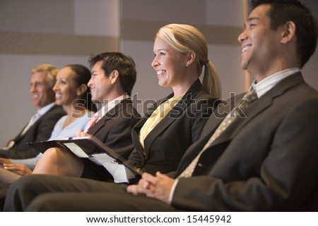 Five businesspeople smiling in presentation room with clipboards - stock photo