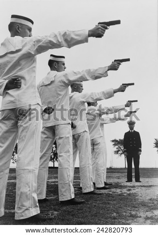 Five cadets at the U.S. Naval Academy, Annapolis, shooting pistols. July 1942. - stock photo