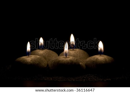 Five candles in the form of stones on a black background - stock photo