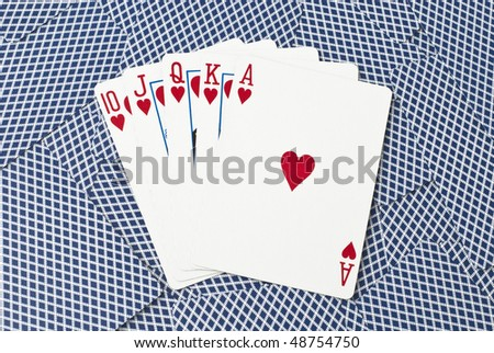 Five cards, showing a royal flush with hearts from ten to ace, on a background of backsides of blue playing cards - stock photo