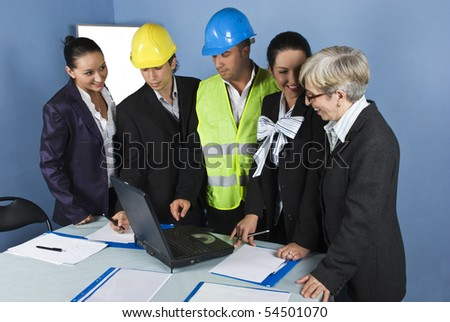 Five cheerful  architects team in office having  a meeting  and they discussion around a table with paperwork and laptop - stock photo