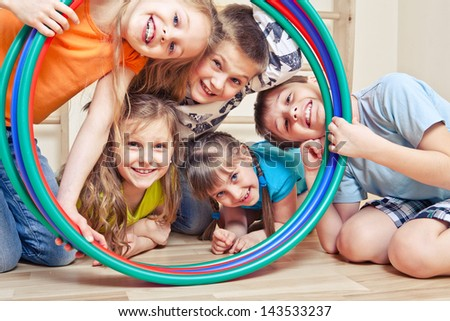 Five cheerful kids looking through hula hoops - stock photo