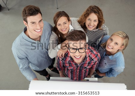 Five Cheerful Young Workmates Smiling at the Camera from High Angle View Inside the Office. - stock photo