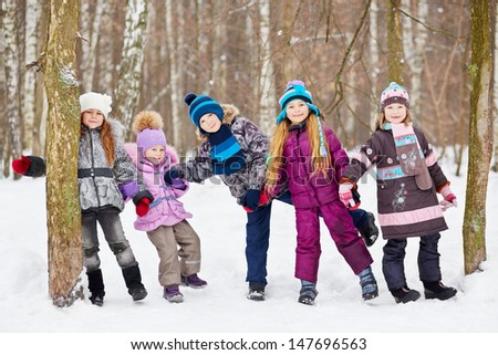 Five children play in winter park tugging hands between two trees - stock photo