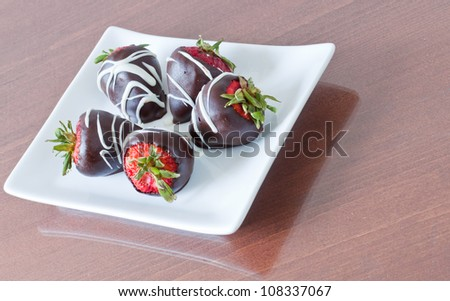 five chocolate covered strawberries served on a white plate - stock photo