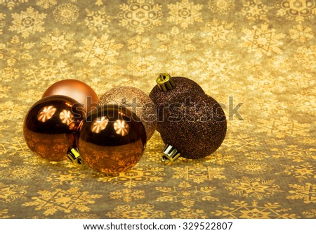 Five Christmas baubles ln a group on the Christmas brownish-yellow stars background.Horizontal view. - stock photo
