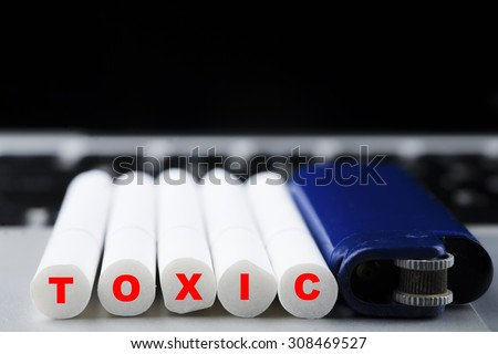 """Five cigarettes sets in a row with blue lighter with red """"TOXIC"""" text on butt on laptop keyboard, unhealthy and lifestyle concept - stock photo"""
