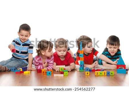 Five clever children are playing on the floor in the kindergarten - stock photo