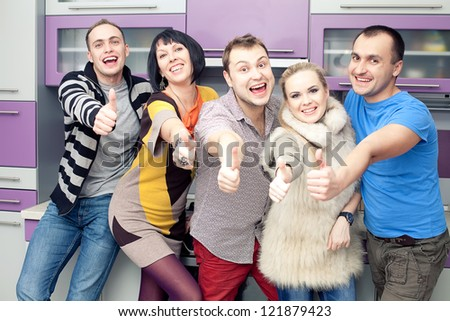 Five close friends enjoying a social gathering together and showing thumbs up happily at home (kitchen room). Indoor shot. - stock photo