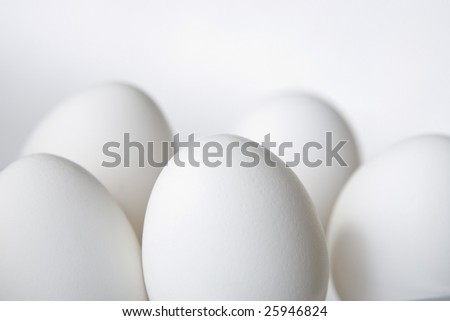 Five eggs isolated on white with center egg in critical focus. - stock photo