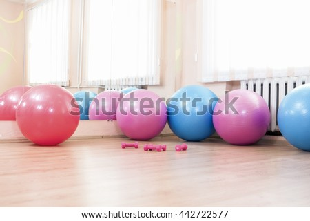 Five Fitballs and Barbells On Floor in Sport Fitness Center Indoors. Horizontal Image Orientation - stock photo