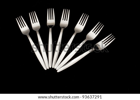 Five forks arranged on a black background - stock photo