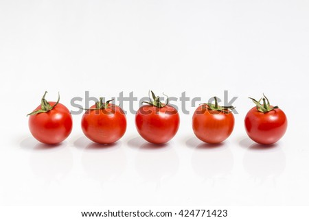 Five fresh tomatoes in a row,  isolated on white - stock photo