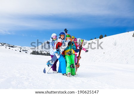 Five friends together with snowboards and skis - stock photo