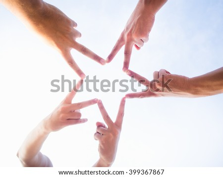 Five friends uniting their hands to make a star - stock photo