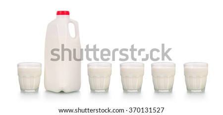 Five full glasses of milk by plastic bottle with red cap on white background - stock photo