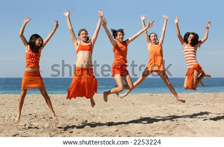 Five girls in orange clothes jumping on the beach - stock photo