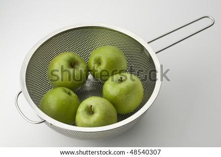 Five Granny Smith Apples in a Colander - stock photo