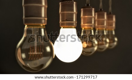 Five hanging vintage incandescent light bulbs over dark background with one illuminated - stock photo