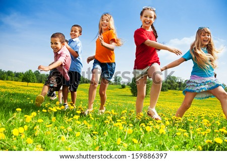 Five happy diversity looking children running in the park - stock photo