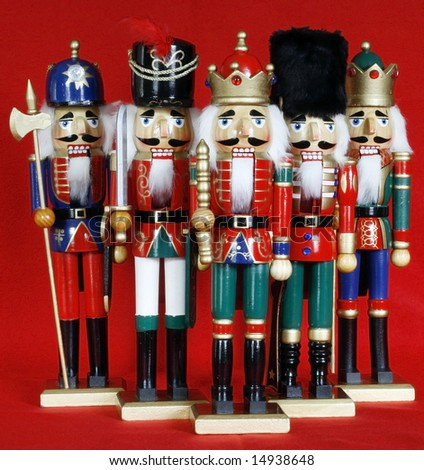 five holiday nutcrackers with red background - stock photo