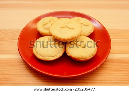 Five homemade Christmas mince pies served on a red plate, on a wooden table - stock photo