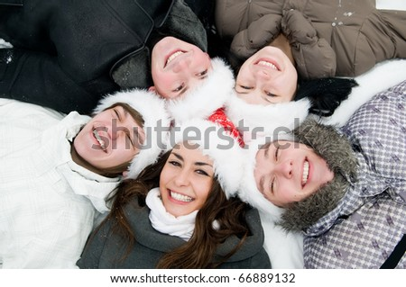 five jolly young boys and girls lying round on snow in winter wearing red hat - stock photo
