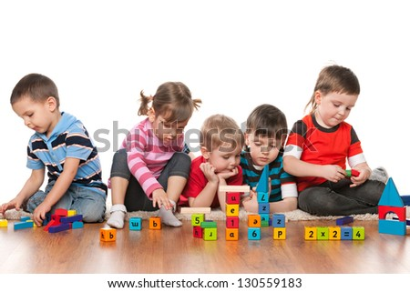 Five kids are playing on the floor with blocks in kindergarten - stock photo