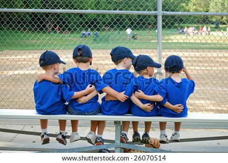 five little boys put their arms around each other while waiting for  their baseball game to start - stock photo