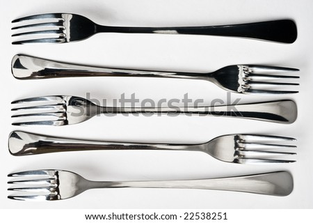 Five metallic forks on gray background - stock photo