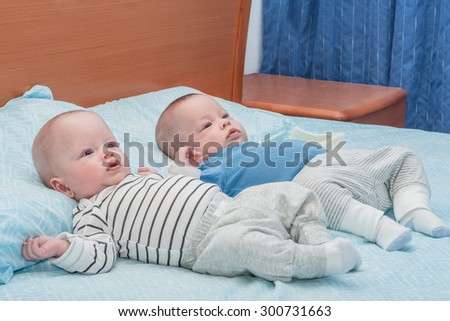 Five-months twins lie on a big bed - stock photo