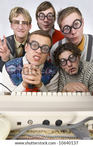 Five nerdy guys sitting in front of old-fashioned keyboard. They are looking at camera. One of them is holding joystick. Front view - stock photo