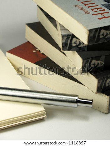 five old black novel books pile one notepad and one pen - stock photo