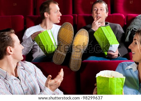 Five people - amongst them a couple - in cinema theater watching a movie, they eating popcorn - stock photo