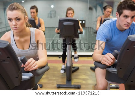Five people at spinning class in gym - stock photo