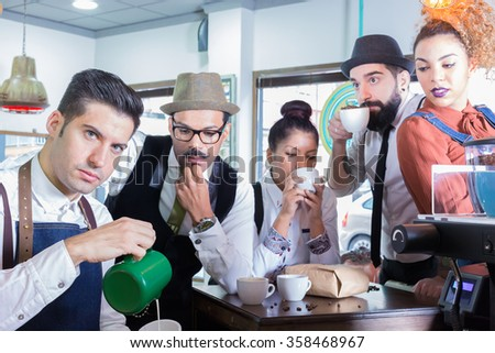 Five people in cafe drinking coffee, barista pouring milk in cup. - stock photo