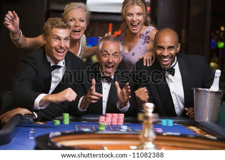 Five people in casino playing roulette smiling - stock photo
