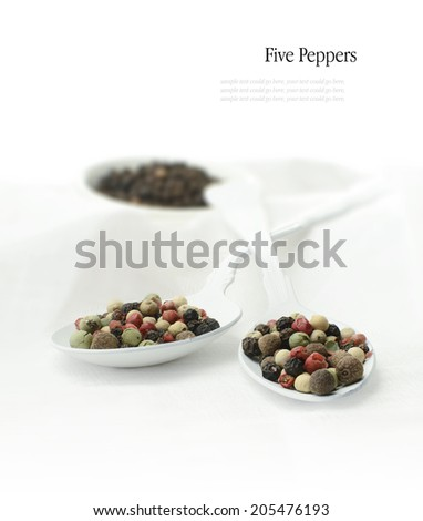 Five pepper kernels on white spoons against a white background. Copy space. - stock photo