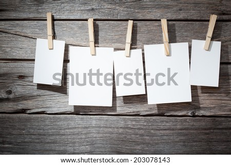 five photo paper attach to rope with clothes pins on wooden background - stock photo
