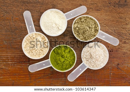 five plastic measuring cups of different superfood supplement powders (form bottom clockwise: wheatgrass, maca root, whey protein, hemp seed protein, psyllium husk) on grunge wood background - stock photo