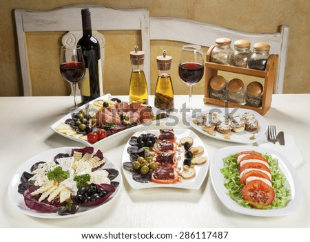 Five plates with appetizer, two glasses and a bottle of red wine, spice oil and jars with spices served on the table. - stock photo
