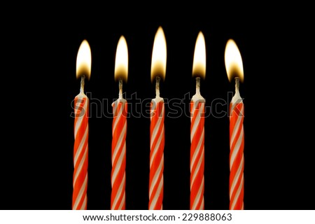 Five red burning candles on black background  - stock photo