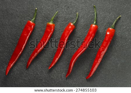 Five red chilli peppers on dark grey limestone - stock photo