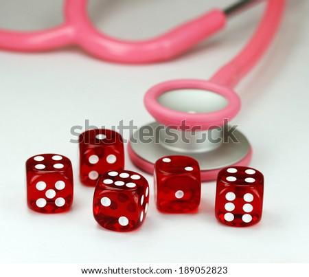 Five red translucent dice with white dots on them in front of a pink stethoscope, asking the question do you gamble with your health? - stock photo