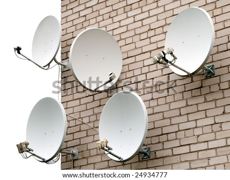 Five satellite antennas on the home front on the background wall of bricks - stock photo