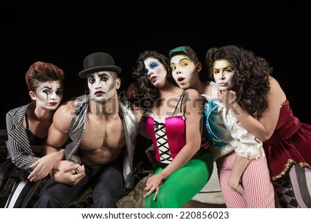 Five serious cirque clowns on theater stage - stock photo
