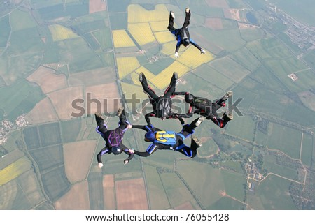 Five skydivers in freefall doing formations - stock photo