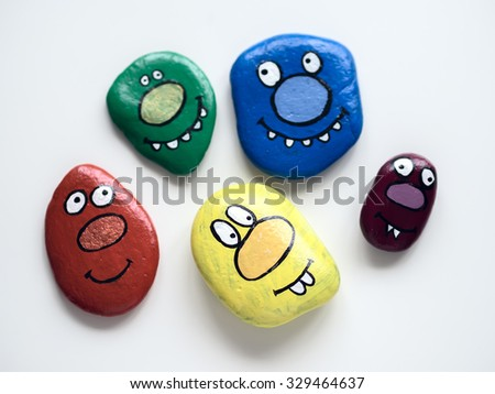 Five smiling faces of monsters. Funny painted acrylic pebbles. Daylight, on a white background with shadows. The correct orientation of individuals. - stock photo
