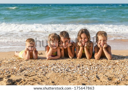 Five smiling kids enjoying on the beach - stock photo